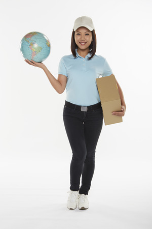 Delivery person carrying a cardboard box and holding up a globe Stock Photo - 22827915