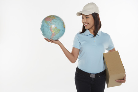Delivery person carrying a cardboard box and holding up a globe photo