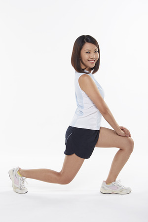 lunges: Woman stretching and doing lunges, facing left Stock Photo
