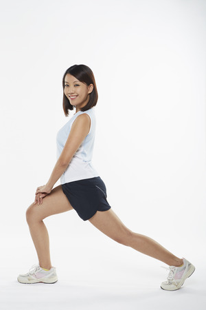 lunges: Woman stretching and doing lunges, facing right