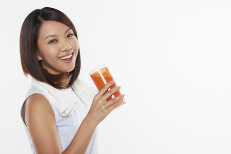 Woman holding a glass of carrot juice photo