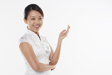 Woman in traditional clothing smiling and showing hand gesture photo
