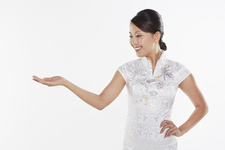 facing right: Woman in traditional clothing smiling and showing hand gesture, facing right Stock Photo