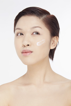 Woman with lotion on her face photo
