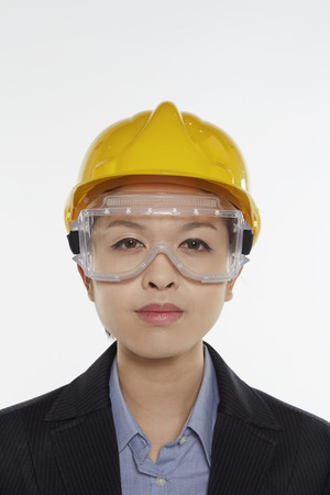 Businesswoman with safety glasses and construction helmet smiling at the camera photo