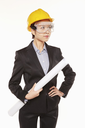 Woman with construction helmet and safety glasses holding a roll of paper photo