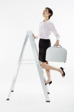 Businesswoman climbing up a ladder while carrying briefcase photo