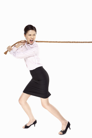Businesswoman pulling a tightrope