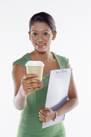 Businesswoman having a drink while holding document photo
