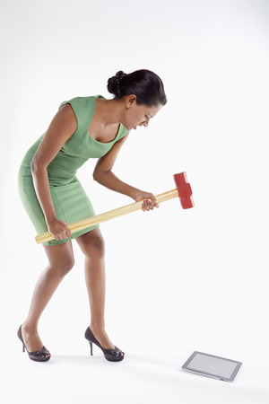 Businesswoman smashing digital tablet with a hammer photo