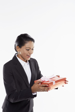 red gift box: Businesswoman handing out a red gift box