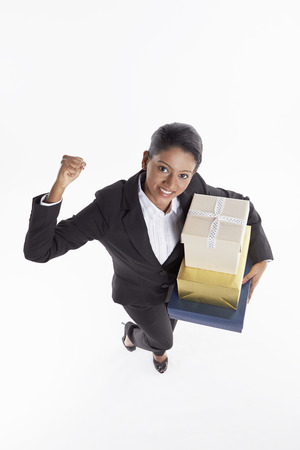 Businesswoman carrying a stack of gift boxes and cheering photo