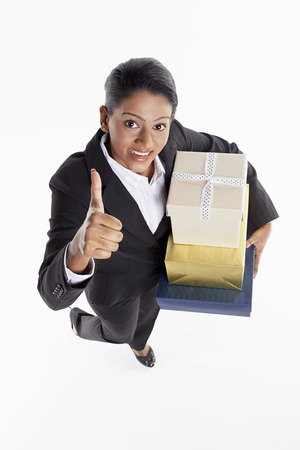 Businesswoman carrying a stack of gift boxes and giving thumbs up photo