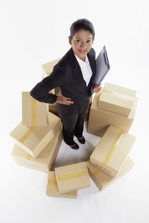 Businesswoman standing in the middle of cardboard boxes photo