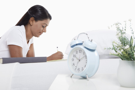 Woman writing notes while laying on bed photo