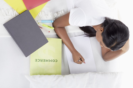 obscured face: Woman writing notes while laying on bed