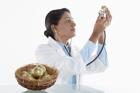 medical personnel: Medical personnel examining a golden egg Stock Photo
