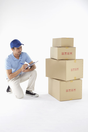 Delivery man doing inventory on boxes photo