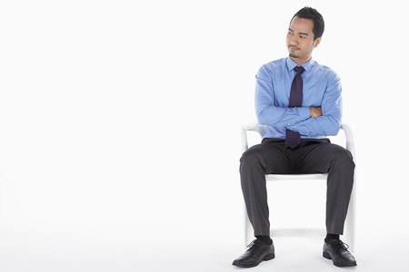 facing right: Businessman sitting on a chair, facing right Stock Photo
