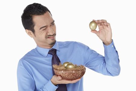 Businessman examine a golden egg