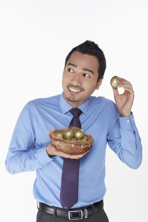 Businessman putting golden egg close to ears photo