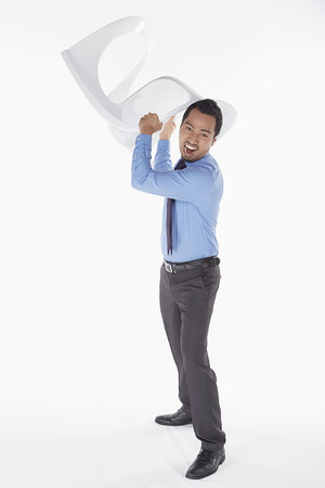 bad temper: Businessman holding a chair in anger Stock Photo
