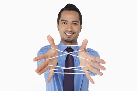 Businessman forming a cats cradle Stock Photo