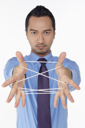 Businessman forming a cats cradle photo