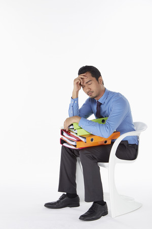 Businessman napping on the chair with folders on lap photo