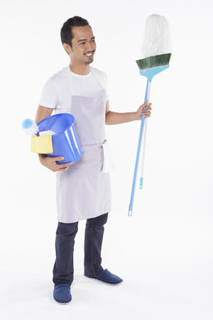 Man holding a variety of cleaning supplies photo