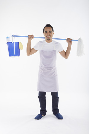 Man carrying mop and bucket on his back photo