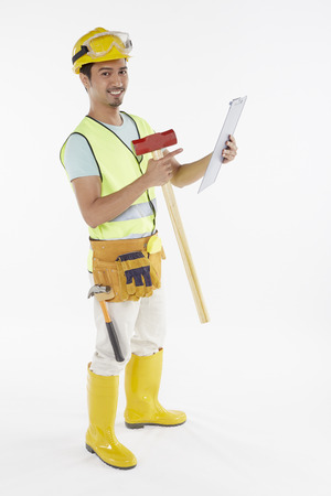 Construction worker holding a hammer and clip file photo