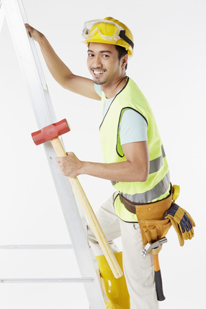 only mid adult men: Construction worker climbing up a ladder Stock Photo