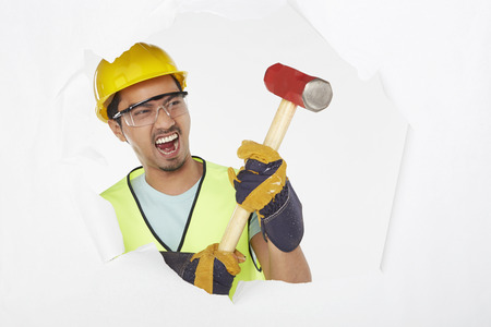 Construction worker knocking wall with a hammer photo