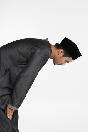 reciting: Man bending at the waist until his palms touch his knees, staying still