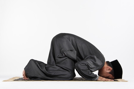 only mid adult men: Main kneeling and staying prostrate by pressing forehead, and placing palms, knees and pads of the toes on the floor. Stock Photo