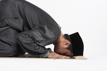 reciting: Main kneeling and staying prostrate by pressing forehead, and placing palms, knees and pads of the toes on the floor. Stock Photo