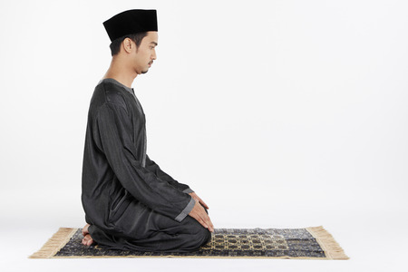 Man sitting in between two Sujuds photo