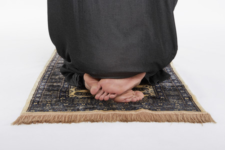 reciting: Man sitting in between two Sujuds Stock Photo