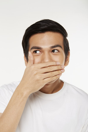 Man covering mouth with hand Stock Photo