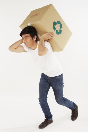 Man carrying a very heavy recyclable box photo