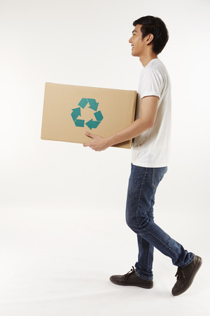 Cheerful man carrying a recyclable cardboard box photo
