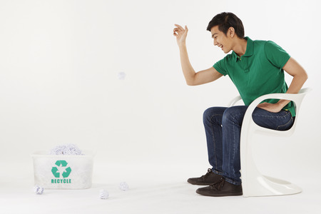 Man tossing crushed paper into a plastic box photo