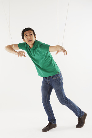 Man being pulled by strings, like a puppet photo