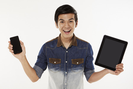 Man holding up a mobile phone and digital tablet photo