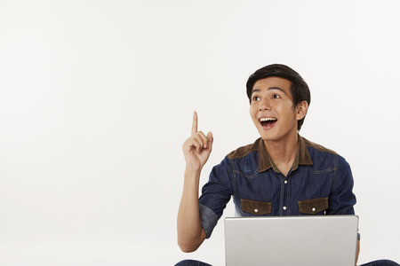 Man holding up index finger while using laptop photo