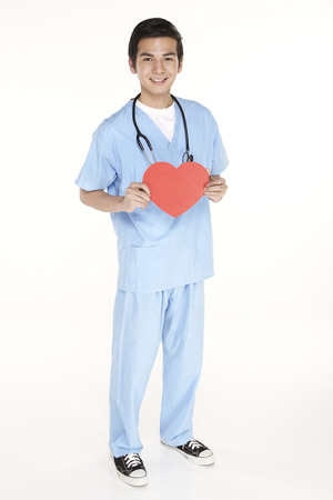 Medical personnel holding a cut out heart shape photo