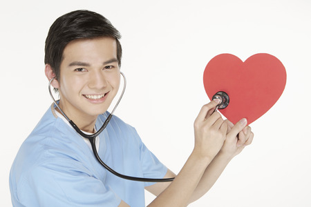 Medical personnel placing stethoscope on cut out heart shape photo