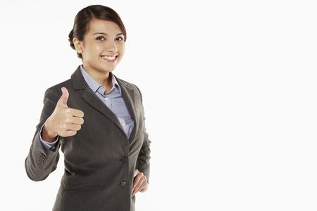 Cheerful businesswoman showing hand gesture photo