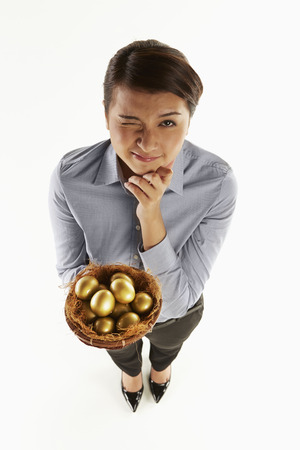 Businesswoman holding a nest filled with golden eggs photo